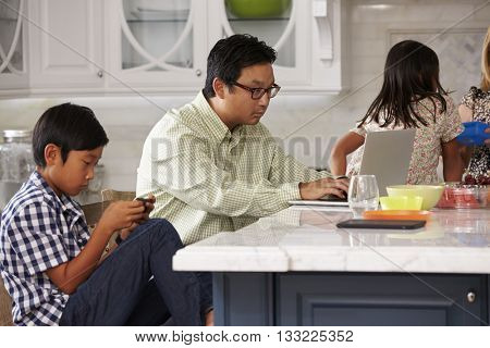 Family In Kitchen Having Breakfast And Using Digital Devices