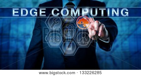 Business person is touching EDGE COMPUTING on an interactive virtual control display. Information technology metaphor and business concept for resource intensive distributed computing services.
