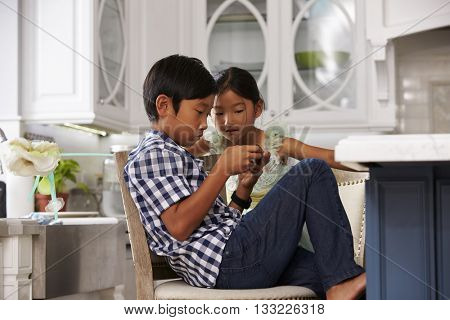 Asian Children Playing Games On Mobile Devices In Kitchen