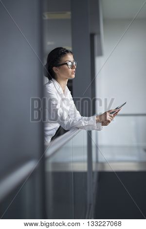 Strong confident business woman standing in an office building hallway holding tablet computer