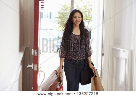 Woman Opening Front Door Of Home Carrying Grocery Bags