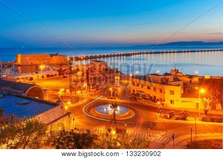 Aerial view of old harbour of Heraklion with Venetian Koules Fortress and marina during blue hour after sunset, Crete, Greece.