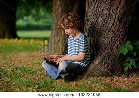 The boy with the tablet in hands sits under a big tree. He sits having crossed legs. The boy attentively looks at the screen. In ears at the little boy earphones.Behind his back trunk of a huge tree