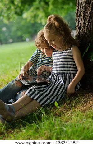 Boy and girl looking at the laptop screen. Children sit together on a grass having leaned against a trunk of a big tree.They hold on a lap the small laptop. To children it is cheerful.