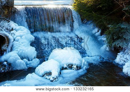 Winter scene with water falling from icy rocks