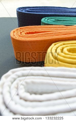 Martial art colored belts, orange green blue and yellow