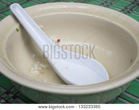 Dirty empty bowl and spoon after eat on the table in the restaurant