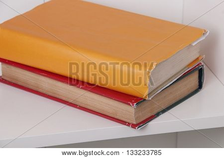 Two books in color cover on wooden bookshelf. Back to school.