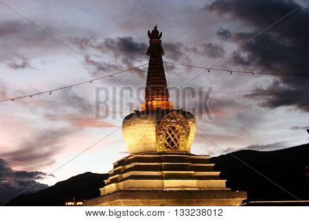 Tibetan Stupa in front of Potala Palace at night with lights on Lhasa Tibet China