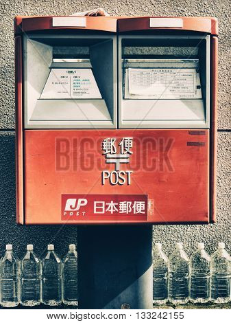 Tokyo - June 2016: Post Box with row of water bottles.