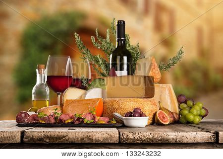 Delicious cheeses with red wines on old wooden table, close-up.