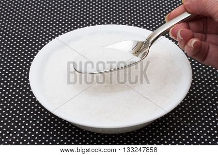 Eating to much sugar White bowl filled with sugar with a spoon on a black and white polka dot background