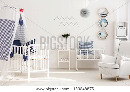 Infant bedroom with simple white furniture and decorations in marine style