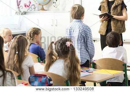 Elegant teacher checking the pupils' presence during lesson. Little standing by his bend