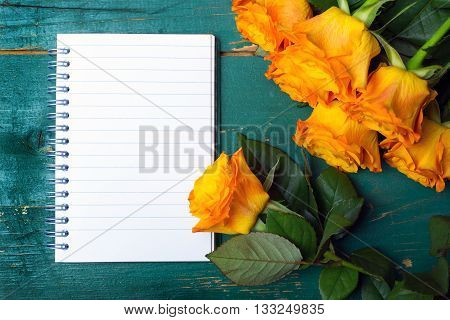 bouquet of orange roses and blank notebook on green wodden background