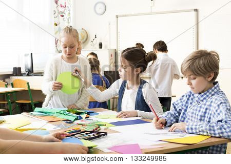 Happy pupils painting the pictures during art classes at school. Sitting with friends by one desk