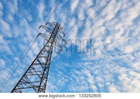 Electricity transmission pylon against blue sky with fluffy clouds. Copyspace