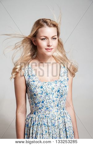 Studio shot of attractive young blonde woman with windy hair in floral dress looking away.