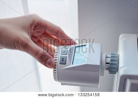 Woman Adjusting Temperature Of Home Heater