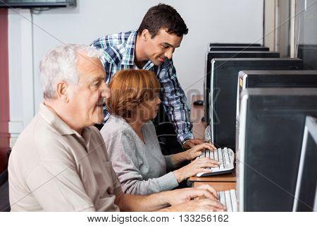 Tutor Assisting Senior Woman In Using Computer