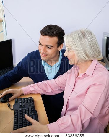Teacher Assisting Senior Woman In Using Computer