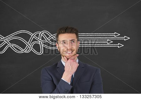 Businessman is standing in front of chalkboard background with drawn arrows Thinking about structuring business process and solutions