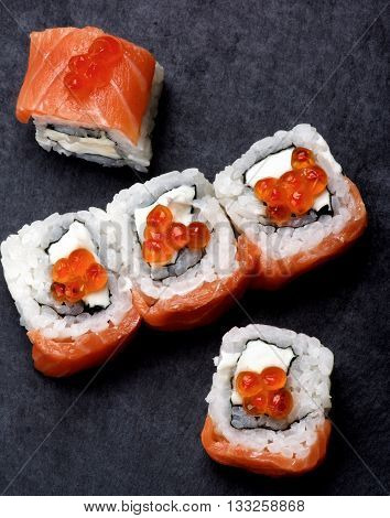 Delicious Sushi with Smoked Sliced Salmon and Gourmet Red Caviar closeup on Stone Plate. Top View