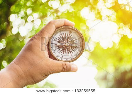 Compass On Hand And Green Bokeh With Sunlight.