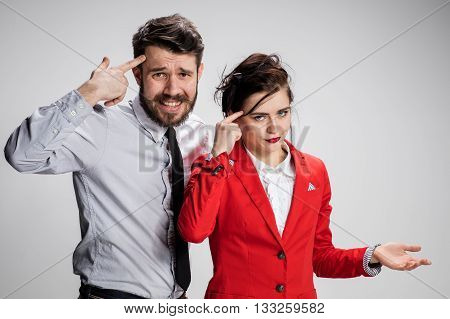 The funny sad business man and woman conflicting on a gray background. Business concept  of relationship of colleagues. concept - you're crazy