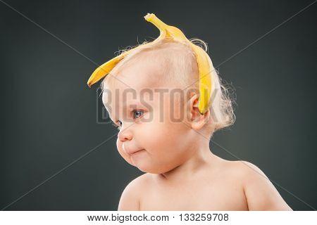 Portrait of cute baby with banana peel on head