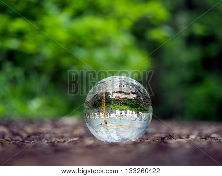 Glass ball in the forest. In the bowl of the construction of the city, crane. Glass - a material, concepts and themes, concepts, environment, nature, ecology, construction, building