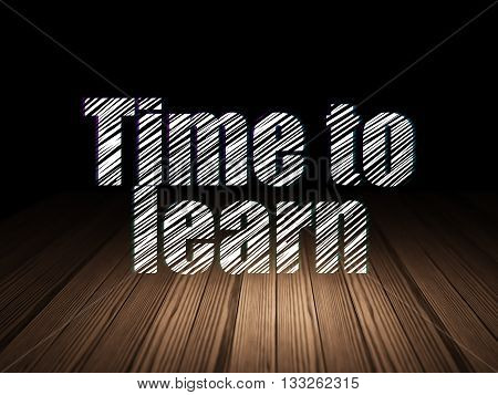 Studying concept: Glowing text Time to Learn in grunge dark room with Wooden Floor, black background