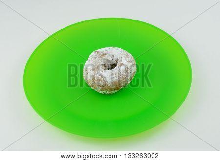 Powdered sugar doughnut on bright green plate