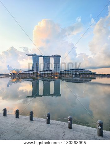 Singapore central quay with reflection on foreground. Modern city architecture at sunrise