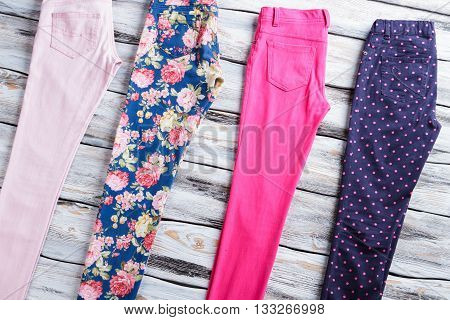 Casual trousers of different color. Navy and pink pants. Female pants on wooden table. Choose what suits you best.