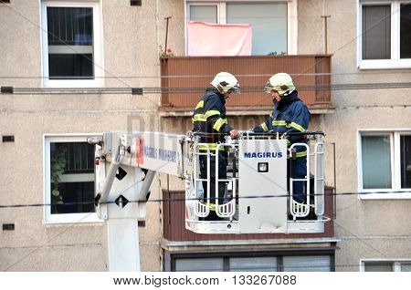 Bytca, Slovakia - June 4, 2016: Two firefighters uprise into telescopic boom basket of fire truck block of flats in background