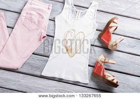 White tank top and sandals. Bead necklace and summer shoes. Best quality guaranteed. Lady's apparel in outlet shop.
