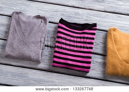 Pink striped sweater. Folded pullovers of different color. Woman's sweatshirt on gray table. Autumn clothing at low price.