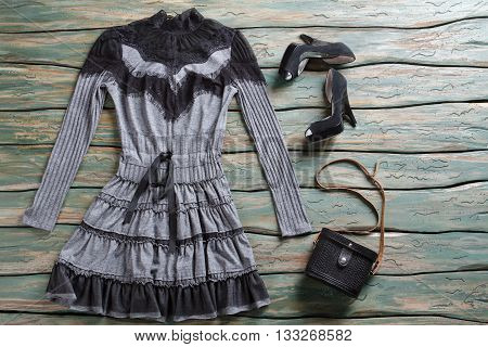 Dark dress and heel shoes. Black heels and small purse. Classic bag with strap. Set of clothes on auction.