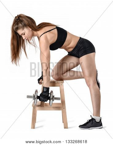 Cutout portrait of muscular young woman lifting a dumbbell for training of the back muscles leaning on the chair. Power training. Power of body. Sportswear for training. Fitness and sport. Healthy lifestyle.
