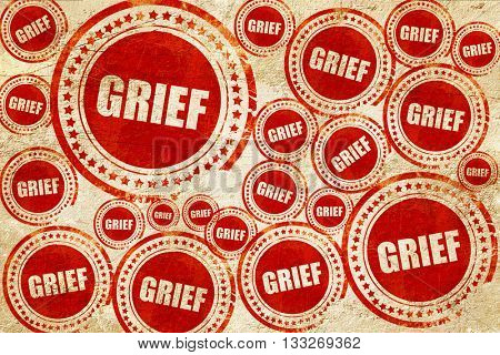 grief, red stamp on a grunge paper texture