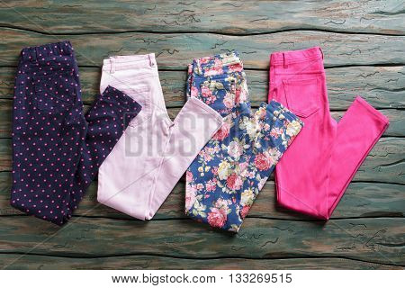 Dark trousers with dotted print. Colorful pink folded pants. Discounted goods in outlet shop. Last sizes at special price.