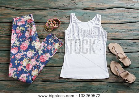 Floral trousers and tank top. Beige sandals and white top. Girl's newly purchased clothing. Set of colorful bracelets.