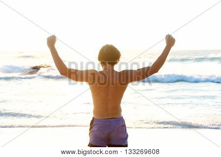 Man From Behind With Arms Outstretched In Front Of Sea