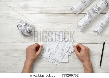 Man hands on wooden table with teared designs and pen. Process of drawing. Failure. Workplace of architect or constructor. Engineering work. Construction and architecture.