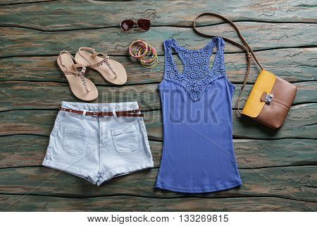 Blue tank top and shorts. Light blue shorts with belt. Woman's outfit with stylish sunglasses. Leather bag from new collection.