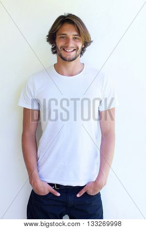 Smiling Man With Hands In Pockets On White Background
