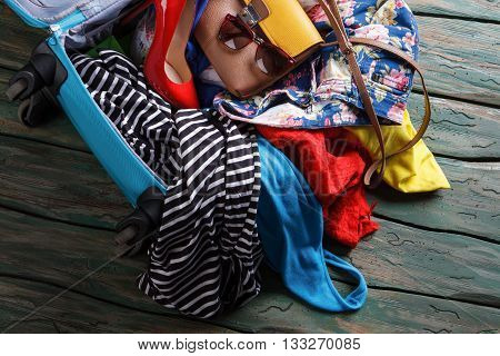 Crumpled clothes in blue suitcase. Heel shoe in opened bag. Trip will take a while. Just a few more things.