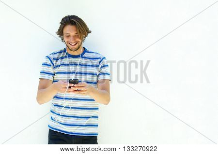 Smiling Handsome Man Looking Down At Mp3 Player