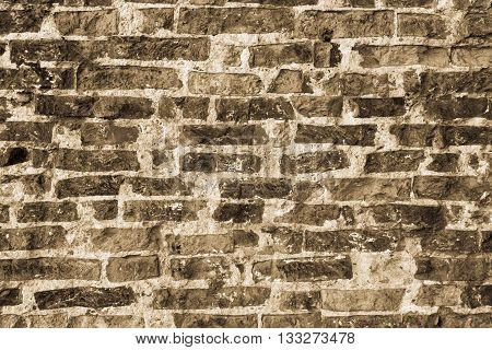 texture of the old destroyed brick wall for a rough vintage background or for ancient wallpaper of color sepia